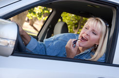 Woman Putting on Lipstick While Driving Stock Images
