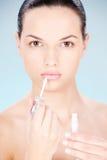 Woman putting lipstick on her lips Stock Photo