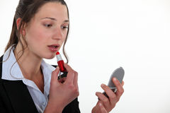 Woman putting lipstick on. Inside Royalty Free Stock Image