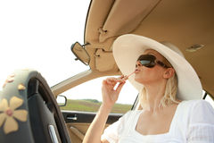 Woman putting lipstick on using the car mirror Royalty Free Stock Photos