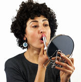 Woman putting on lipstick Stock Photos