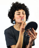 Woman putting on lipstick Stock Photos