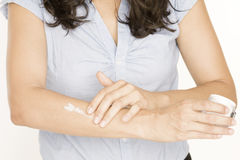 Woman putting lotion on her arm Stock Photos