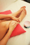 Woman putting lotion on her legs Royalty Free Stock Photography