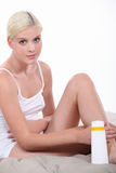 Woman putting lotion on legs. Woman putting lotion on her legs Stock Photos