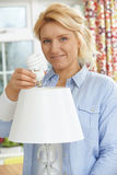Woman Putting Low Energy Lightbulb Into Lamp At Home Stock Image