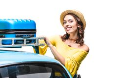 Woman putting luggage on car roof. Young woman putting luggage on car roof isolated on white Stock Photos