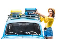Woman putting luggage on car roof. Young woman putting luggage on car roof isolated on white Royalty Free Stock Images
