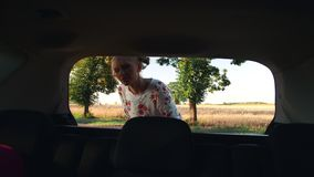 Woman putting luggage into trunk during nice trip through countryside. Woman putting luggage into trunk. Female traveller putting luggage inside car trunk stock footage