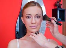 Woman putting on make up Stock Photos