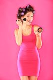 Woman putting make-up. Woman putting makeup getting ready for fun. Funny image of beautiful young female model with hair rollers in pink dress on pink background Stock Photography
