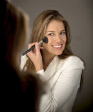 Woman putting make up Royalty Free Stock Images