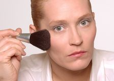 Woman putting on make-up Stock Photography