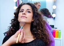 Woman putting make up Stock Photos