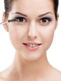 Woman applying makeup with cosmetic brush Royalty Free Stock Photos