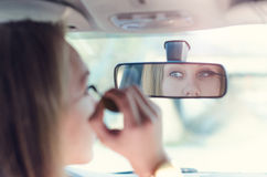 Woman putting make up in a car. Pretty young woman looking in mirror. Dangerous situation. Royalty Free Stock Image