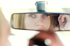 Woman putting make up in a car. Pretty young woman looking in mirror. Dangerous situation. Royalty Free Stock Photography