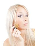 Woman putting make up on her face Stock Photography