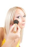 Woman putting make up on her face with a brush Royalty Free Stock Photo
