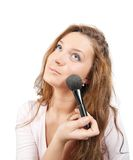 Woman putting make up on her face with a brush Royalty Free Stock Images
