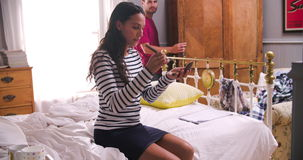 Woman Putting On Make Up And Man Getting Dressed In Bedroom. Woman sitting on bed putting on make up with brush in the morning as man chooses clothes from stock footage