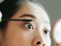 Woman is putting make up mascara on her eyelashes. Asian woman is putting make up mascara on her eyelashes royalty free stock photography
