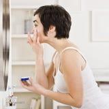 Woman Putting on Makeup Stock Image