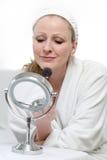 Woman putting on makeup Royalty Free Stock Photos