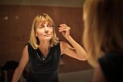 Woman putting makeup royalty free stock photography