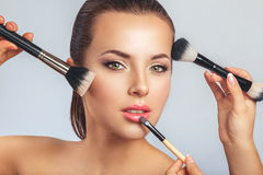 Woman putting makeup on Stock Images