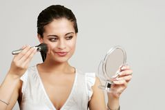 Woman putting on makeup with blush brush. On a grey background Royalty Free Stock Photo