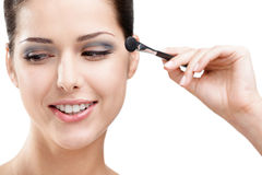 Woman putting on makeup with brush Royalty Free Stock Photo