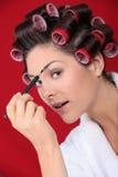 Woman putting on makeup Stock Photography
