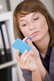 Woman putting on makeup by office work Royalty Free Stock Photography