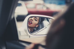 Woman putting on makeup with side view mirror Stock Images