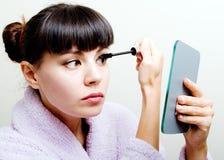 Woman putting mascara. Young beautiful woman looking at the mirror and putting mascara stock photo