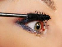 Woman putting on mascara. Closeup of a woman putting on mascara Stock Image