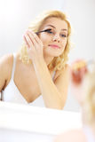 Woman putting on mascara in bathroom Royalty Free Stock Images
