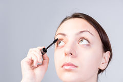 Woman Putting Mascara on Lashes While Looking Up Stock Photography