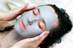 Woman putting a  mask Stock Photos