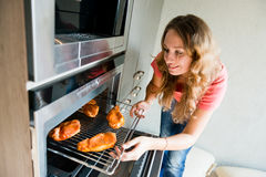 Woman putting meat into oven Stock Photos