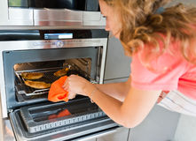 Woman putting meat into oven Royalty Free Stock Images