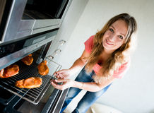 Woman putting meat into oven Stock Image