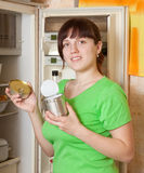 Woman putting with metal can near refrigerator. Young woman putting with metal can near refrigerator at home royalty free stock photo