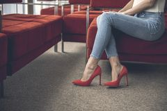 Woman putting on modern footwear. Female wearing beautiful red high heel shoes while sitting on sofa royalty free stock photo