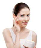 Woman putting on moisture cream from container on face. Woman applying moisture cream from container on face, isolated on white. The pursuit of beauty Stock Image