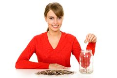 Woman putting money in jar Stock Images