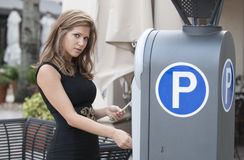 Woman putting money in a parking meter Stock Photography
