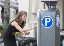 Woman putting money in a parking meter Royalty Free Stock Photography