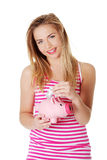 Woman putting money in piggy bank Stock Images
